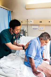 Doctor puts stethoscope on TB patient's back to check breathing
