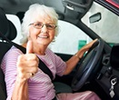 Elderly lady sitting in the driver's seat of her car giving a thumbs up