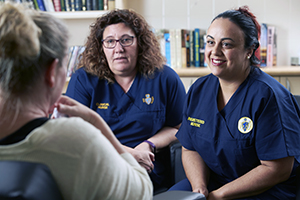 Two female nurses sitting down in conversation with another woman