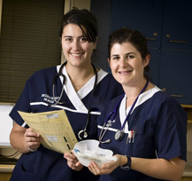 2 registered nurses looking over a patient file