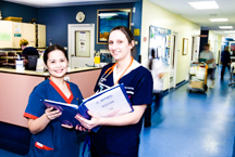 Two nurses looking through procedure's manual