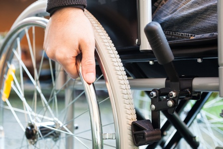 Close up image of a wheelchair user grasping the wheel of a wheelchair.