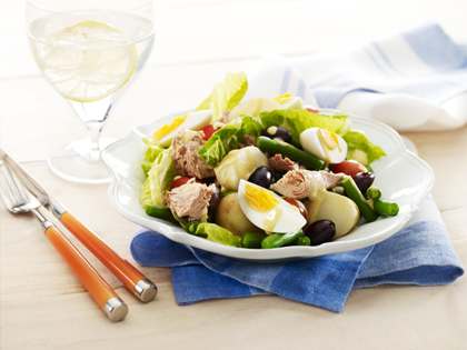 Nicoise salad in a bowl with a glass of water