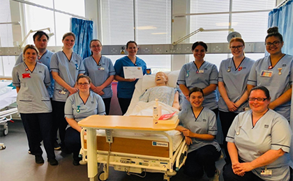 11 graduate nurses and midwives gathered around a training simulation dummy in a hospital bed