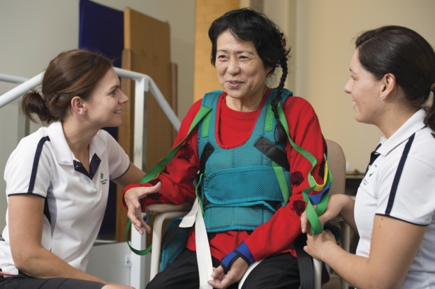Two female health professionals supporting an older patient in physical rehabilitation