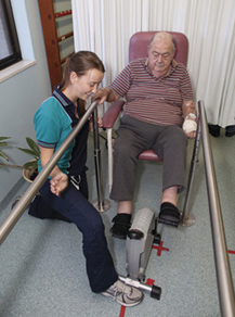 Man participating in rehabilitation therapy with help of physiotherapist