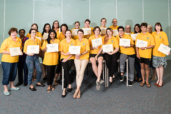 Group of volunteers holding certificates