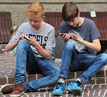 Boys sitting looking at their phones