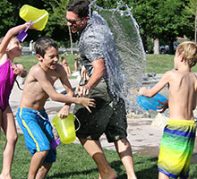 2 young boys, 1 young girl and a male adult having a water fight laughing