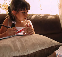 young girl reading on couch