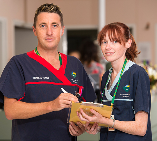 Two nurses checking a chart in a hospital ward