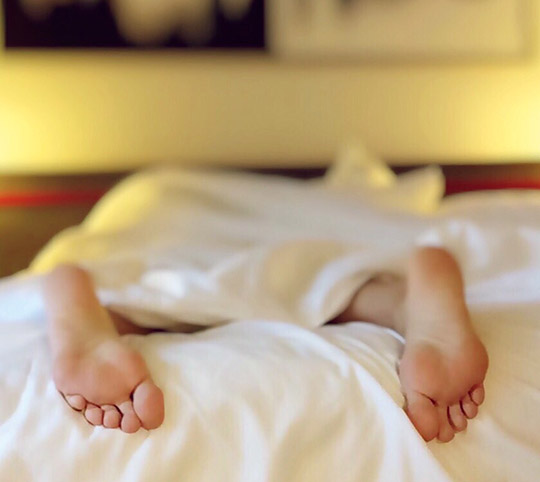Person asleep in bed, close up of feet