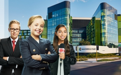 Three children dressed as news readers standing in front of Perth Children's Hospital