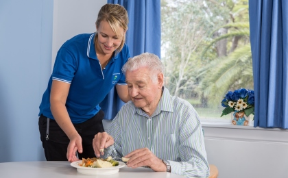 Healthcare worker assisting senior man with food