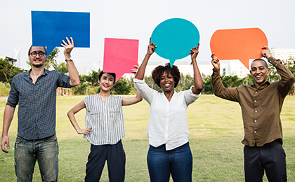 Three people holding blank speech bubbles in a park