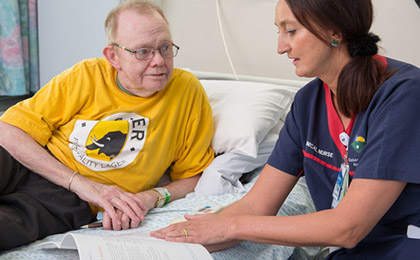 Nurse showing an informational booklet to patient in a hospital bed
