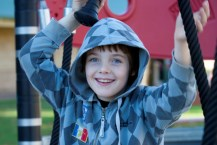 Boy wearing hooded jumper playing in playground