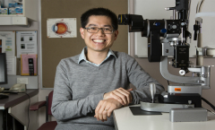 Fred Chen standing next to a microscope in a labratory