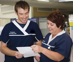 Male and female nurse looking at notes