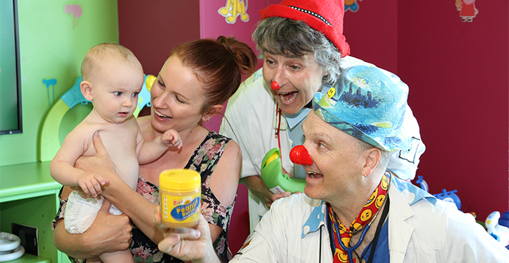 Mother with baby while a male and female dressed as clowns hold a peanut butter jar