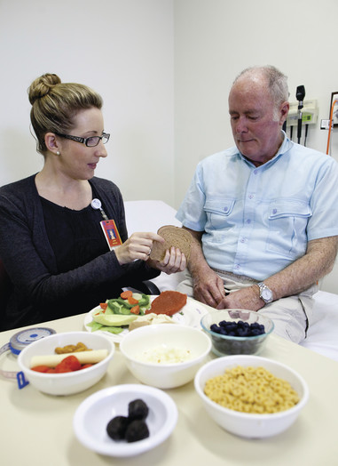 Female health professional showing examples of healthy foods to an older male patient.