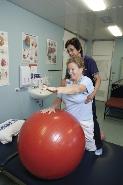 Female health professional assisting older patient with arms exercises