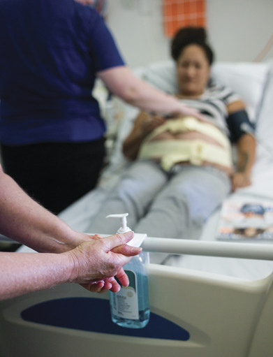 Health care worker using alcohol-based hand rub before treating a patient in hospital