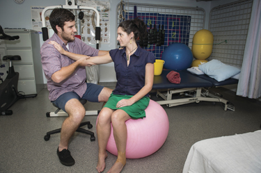 Patient sitting on fit ball while health care professional is holding her arm