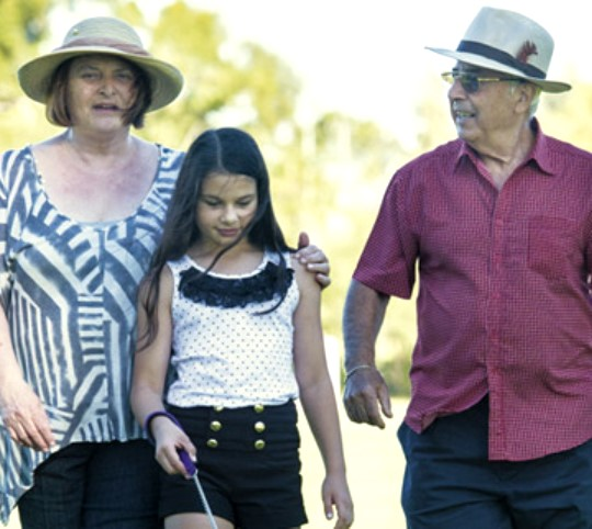 Grandparents with granddaughter walking in park