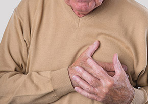 Elderly man grabbing his chest in pain