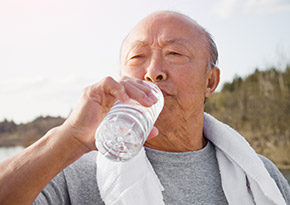 Elderly man drinking a bottle of water after a run