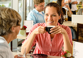 Woman in her 30s drinking coffee with her mum at a coffee shop