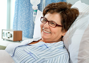 Woman lying in a hospital bed wearing a gown