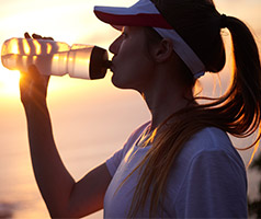 Girl drinking water from a bottle in hot weather
