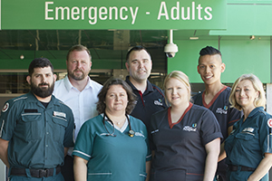 Fiona Stanley Hospital emergency department staff and staff from St John Ambulance stand under a sign that reads' Emergency - Adults.
